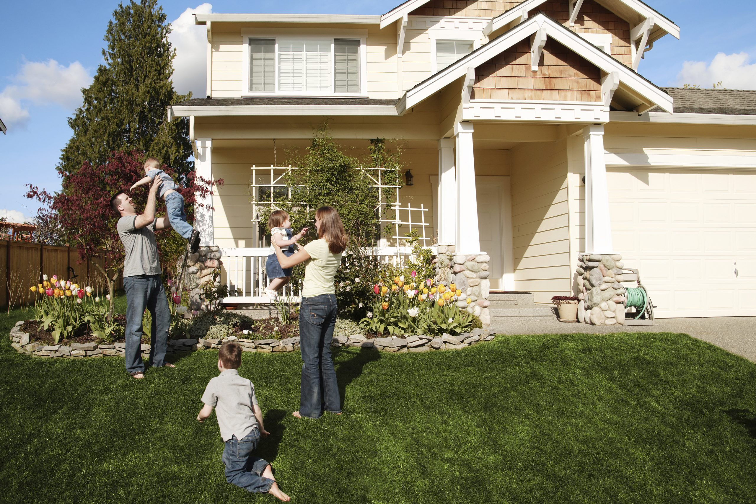 family in front of house - feeling happy and secure